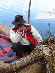 Man sits on his totora reed boat on the floating islands of Uros