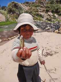 Child displays fish on Taquile Island