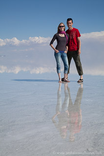 Couple posing in flooded Salar de Uyuni with reflections