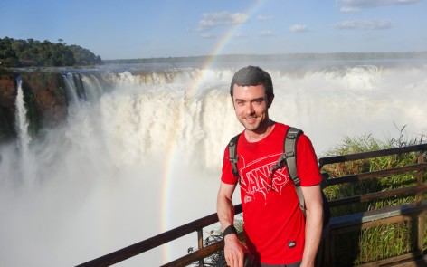Man overlooking Iguazu Falls with rainbow