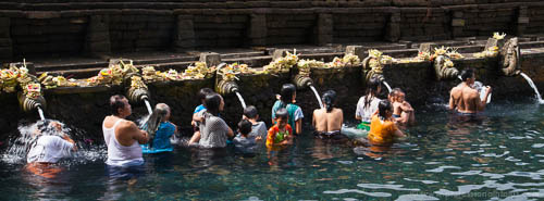 People bathing in the holy spring water at Tampaksiring Temple in Bali